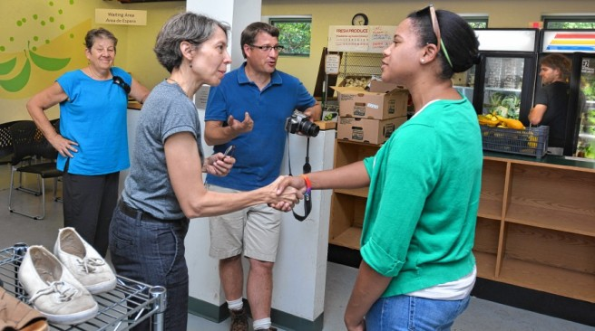 Sarah Pease, second from left, who is the program director of the Northampton Survival Center, shakes hands with Ashley Hackett, who is a program manager of Harvard Pilgrim Healthcare Foundation, beside Pat James, left, and Clem Clay, of Grow Food Northampton, Tuesday at the center. Marvin Warren, background, stocks a cooler with donated vegetables.